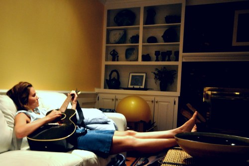 Olivia Conner strums on guitar